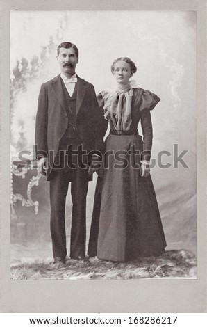US - ILLINOIS - CIRCA 1897 - A vintage Cabinet Card  photo of a young couple. They are both standing. The woman is dressed in a Victorian style dress. A photo from the Victorian era. CIRCA 1897 - stock photo