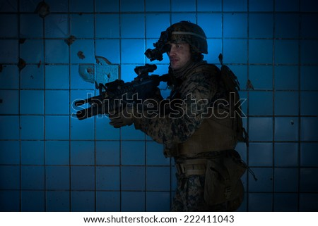 US Marine in a defensive position. Military in the destroyed building with a night vision device. - stock photo