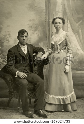 US - MASSACHUSETTS - CIRCA 1890 - A vintage antique photo of a young couple. The husband is sitting while his wife is standing behind the chair. A photo is from the Victorian era. CIRCA 1890 - stock photo