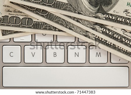 US paper money on white computer keyboard with spacebar. - stock photo
