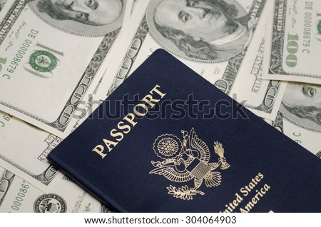 US Passport and pile of US dollar money - stock photo