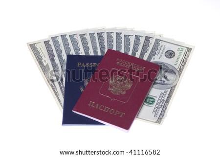 US Passport and Russian passport with stack of US 100 dollars bills - stock photo