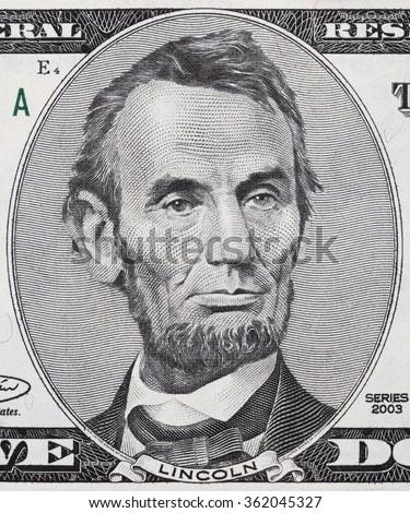 US President Abraham Lincoln face on five dollar bill macro, 5 usd, united states money closeup - stock photo