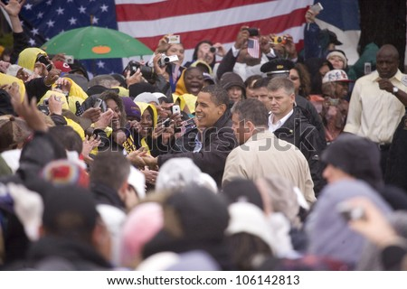 US Senator Barack Obama in pouring rain shakes hands at Presidential Rally on October 28, 2008, at Widener University in Chester, PA - stock photo