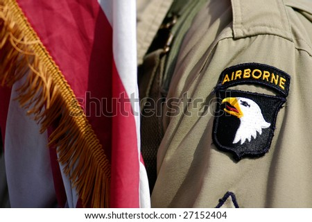 US soldier and flag of Airborne division during a commemorative parade in France - stock photo