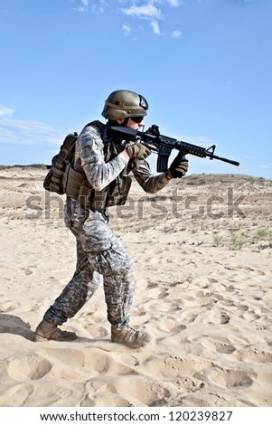 US soldier going through the desert during the military operation - stock photo