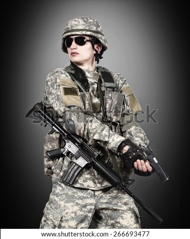 US soldier holding gun on a black background - stock photo