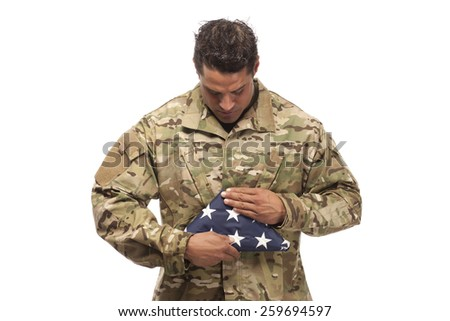 US Soldier looking at folded flag in front of white background - stock photo