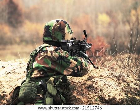 US Soldier shooting his machine gun - stock photo
