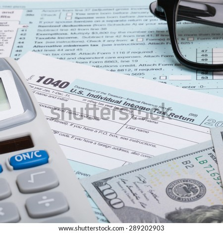 US 1040 Tax Form, calculator, glasses and dollars - close up shot - stock photo