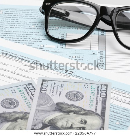 US Tax Form 1040 with glasses and 100 US dollars - stock photo