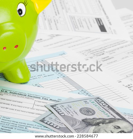 US Tax Form 1040 with green piggy bank - stock photo