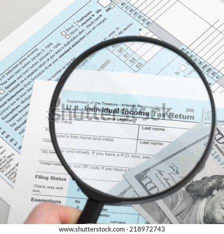 US Tax Form 1040 with magnifying glass and dollars - 1 to 1 ratio - stock photo