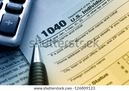 US tax form 1040 with pen and calculator. - stock photo