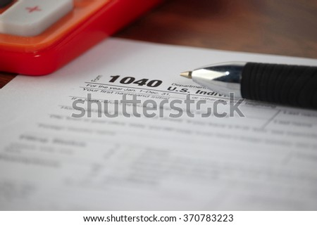 US 1040 tax form with pen and calculator selective focus / taxation concept  - stock photo