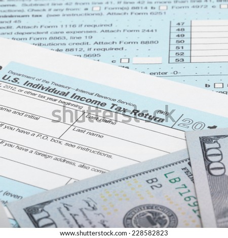 US Tax Form 1040 with 100 US dollar bills - stock photo