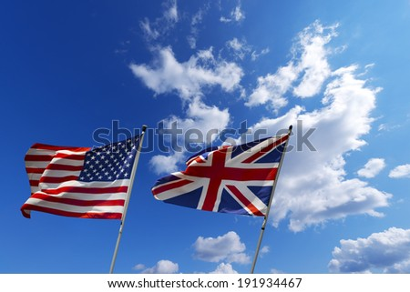USA and UK flags in the blue sky / English and American flag waving in the wind on blue sky with clouds - U.S.A. and UK - stock photo