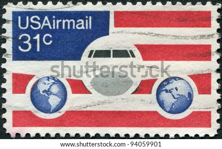 USA - CIRCA 1976: A stamp printed in the USA, shows a Plane, Globes and Flag, circa 1976 - stock photo