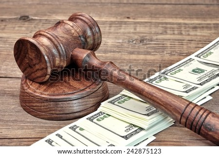 USA Dollar Banknotes and Judges Gavel on Wooden Table - stock photo