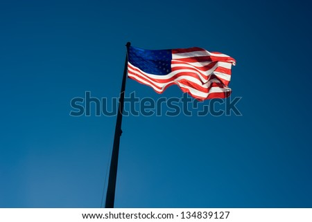 USA flag blows in the wind against a blue sky - stock photo