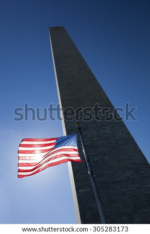 USA flag in the wind dark sky, the sun and Washington Monument - stock photo