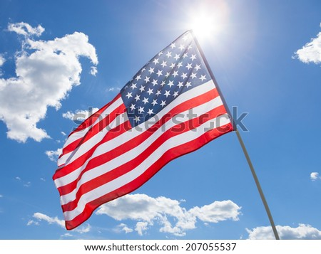 USA flag waving on blue sky background - stock photo