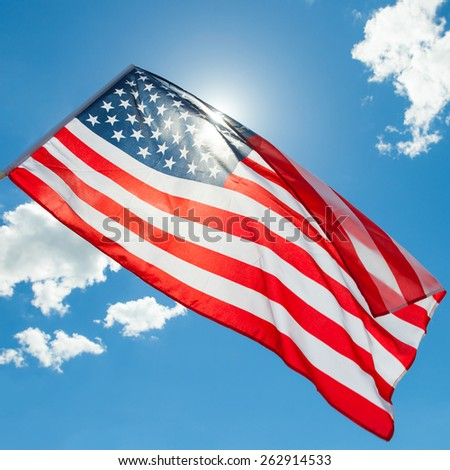 USA flag with clouds - outdoors shoot - stock photo
