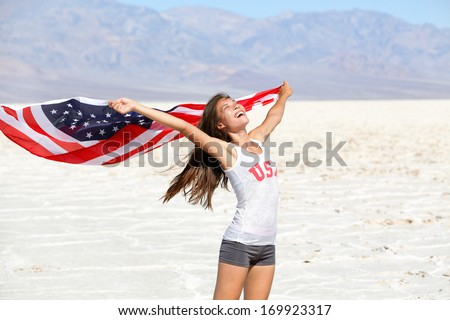 USA flag - woman athlete showing american flag. US sport athlete winner cheering waving stars and stripes outdoors in desert nature. Beautiful cheering happy young multicultural girl joyful excited. - stock photo