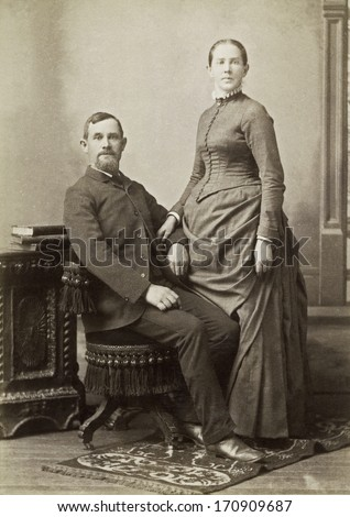 USA - IOWA - CIRCA 1885 - A vintage photo of a young couple. The husband is sitting and the wife is standing. She is dressed in a Victorian style dress. A photo from the Victorian era. CIRCA 1885 - stock photo
