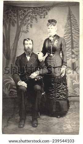 USA MASSACHUSETTS CIRCA 1875  A Vintage Carte De Visite photo of a couple. He is sitting in a chair and she is standing. Photo from the Victorian era. CIRCA 1875 - stock photo
