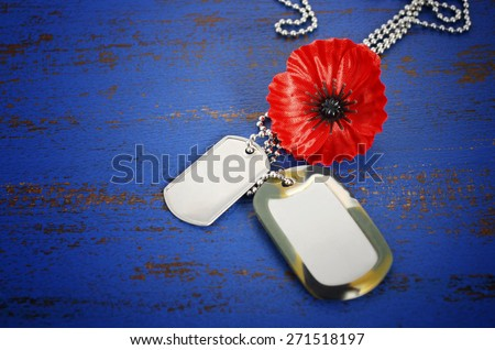 USA Memorial Day concept of red remembrance poppy on dark blue vintage distressed wood table, with soldiers dog tags, and vignette.  - stock photo