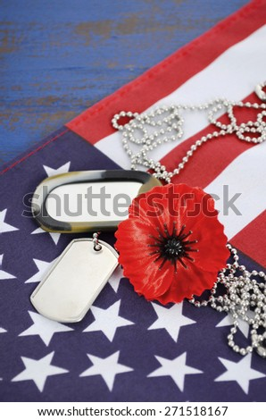 USA Memorial Day concept with dog tags and red remembrance poppy on American stars and stripes flag on dark blue vintage wood table.  - stock photo