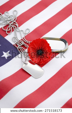 USA Memorial Day concept with dog tags and red remembrance poppy on American stars and stripes flag.  - stock photo
