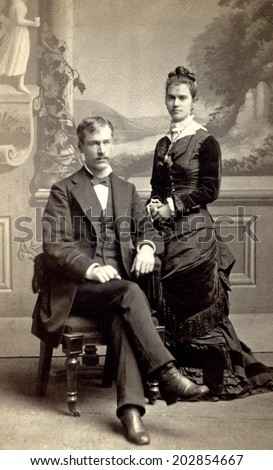 USA - MINNESOTA - CIRCA 1880 Vintage Carte de Viste photo of young couple. The gentleman is sitting and the lady is standing dressed in a Victorian style dress. Photo from Victorian era. CIRCA 1880 - stock photo