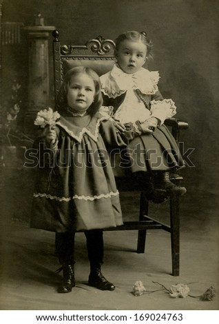 USA - NEW YORK - CIRCA 1895 - A vintage antique photo of two little girl's dressed in Victorian style dress. One is standing and the other one is sitting in. A photo from the Victorian era. CIRCA 1895 - stock photo