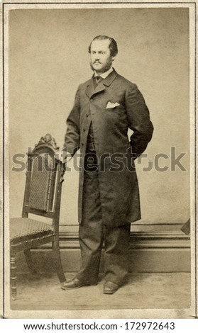 USA - NEW YORK - CIRCA 1862 - A vintage Cartes de visite photo of a gentleman. The man is standing with one hand on a chair. A photo from the Civil War Victorian era. CIRCA 1862 - stock photo