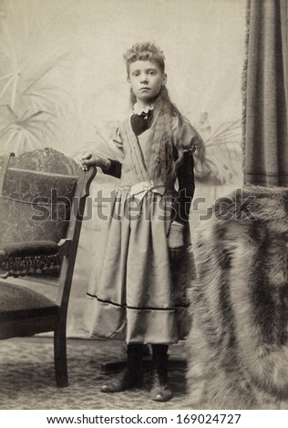 USA - OHIO - CIRCA 1898 - A vintage antique photo of a young girl dressed in a Victorian style dress with long hair. She is standing next to a chair. A photo from the Victorian era. CIRCA 1898 - stock photo