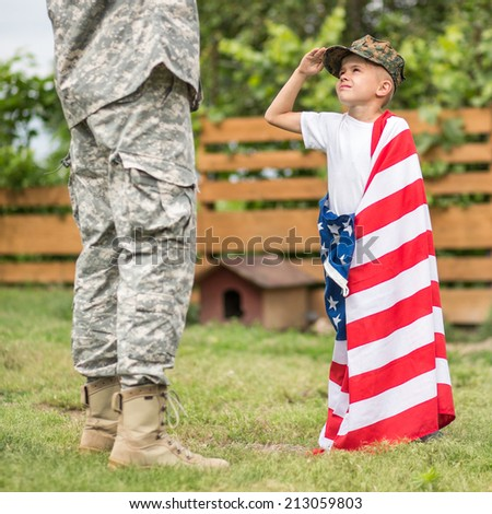 USA patriots concept. Son salutes his father. focus on son. daylight - stock photo