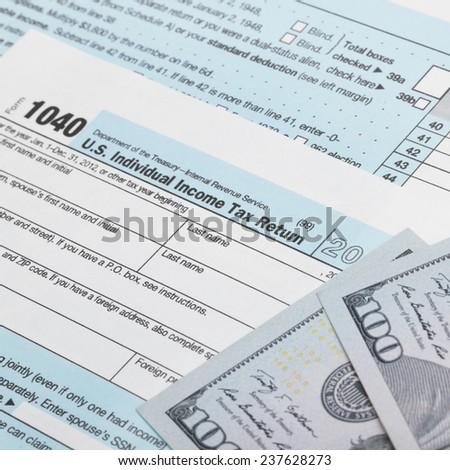 USA Tax 1040 Form 1040 and 100 US dollar bills - stock photo