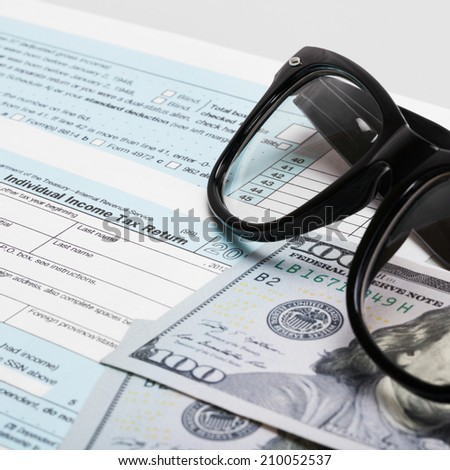 USA 1040 Tax Form with glasses and two 100 US dollar bills - stock photo