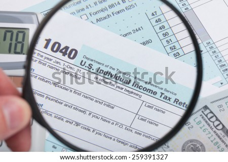 USA 1040 Tax Form with magnifying glass - stock photo