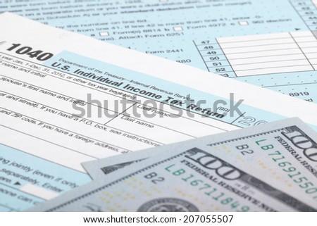 USA Tax Form 1040 with 100 US dollar bills - stock photo