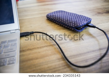 USB external hard disk with soft cute case plug in to notebook - stock photo