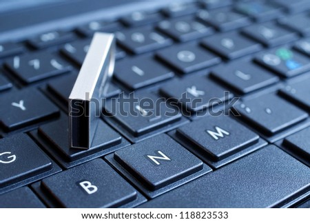 Usb flash drive on pc keyboard. Shallow depth of field. - stock photo