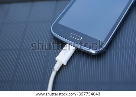 Use of renewable energy - Mobile Phone Chargers on grass in nature with Sun - stock photo