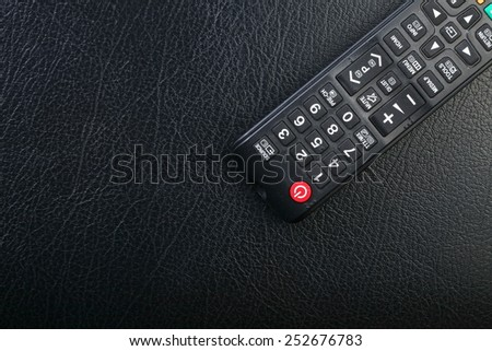 Used and dirty tv remote control put on the black color leather surface background represent the tv technology related. - stock photo