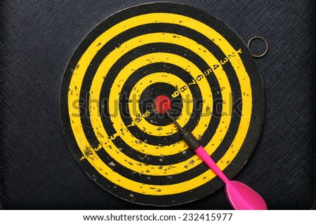 Used and vintage dartboard with arrow in the scene appear a lot of damaged hole from arrow marked put on the black color leather surface as a background represent the entertainment game. - stock photo