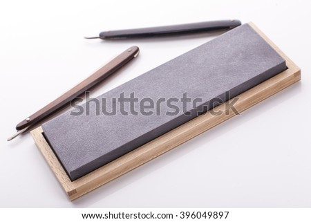 Used Classic Straight Razor, shapening stone, old style, in soft diffuse light. - stock photo