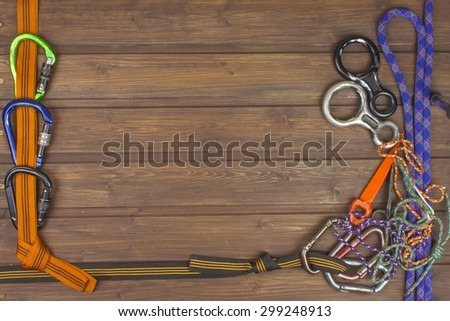 Used climbing gear on wooden background. Advertising boards of trade. The concept of extreme sports. Decoration of older equipment climbers. - stock photo