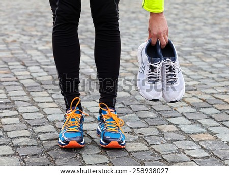 Used dirty pair of running shoes and new ones - stock photo